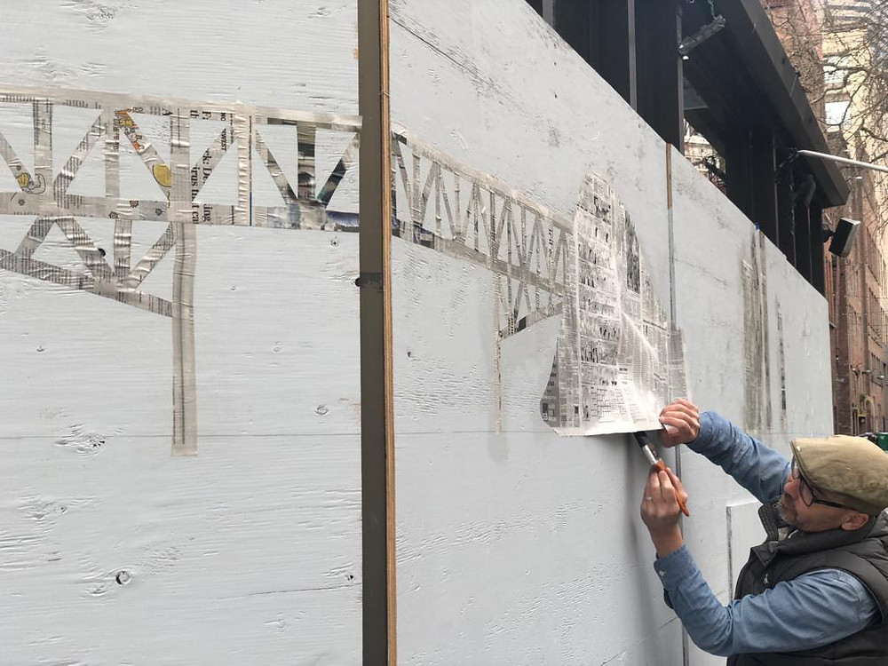 Artist Ray Monde pasting up a cut out of a 1950s bridge