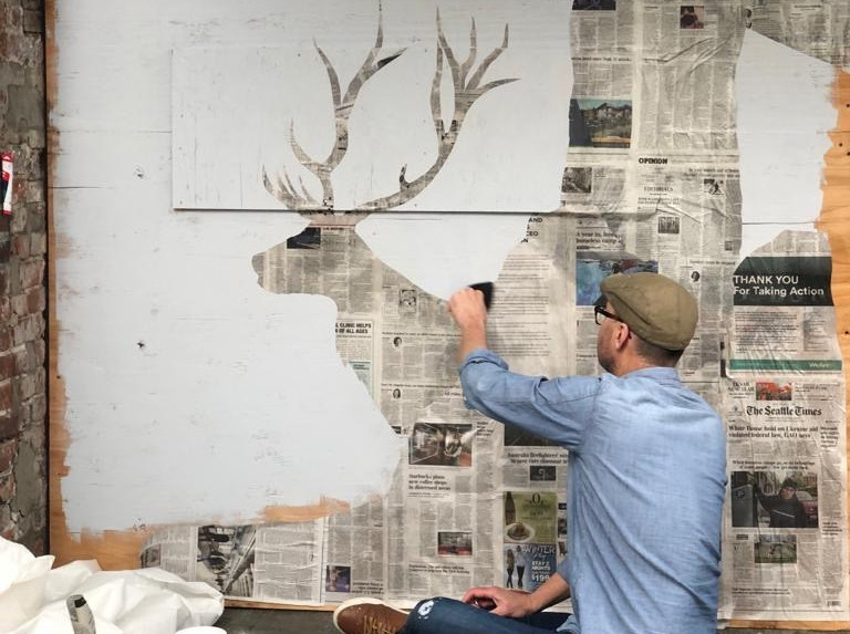 Artist Ray Monde wheatpasting a paper cut out of an elk
