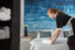maid-laying-towels-on-bed-P8DXHAB.jpg