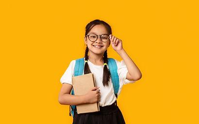 joyful-korean-kid-girl-holding-book-posi