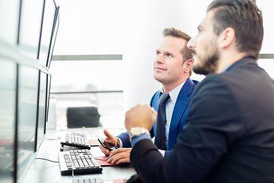 Dois homens olham para tela do computador
