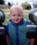 blue-eyed toddler smiling to depict toddler parent coaching