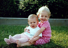 a baby and a toddler sitting on a lawn to depict baby parent coaching