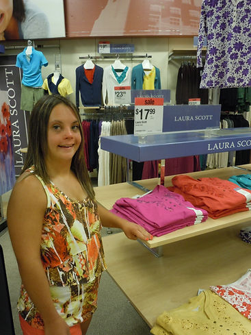 Alt=AHEDD Participant Jenna, standing next to a clothing display at Sears