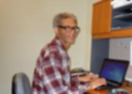 Alt=AHEDD Participant Martin, sitting at his desk using a laptop