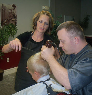 Alt=AHEDD Participant Matt cutting the hair of a small male chiled with the assistance of his boss, Julie