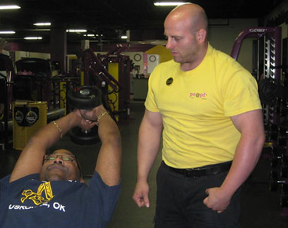 Alt=AHEDD Participant Nathan- Fitness Trainer Assisting Another Person with Weights
