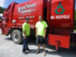 Participant Edward, standing by the red waste management truck his company uses to compact and transport waste