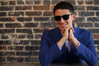 JK smiling wearing sunglasses, in blue suit, elbows on table, chin resting on folded hands.