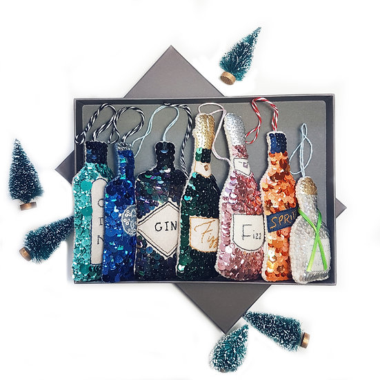 A grey gift box with sequinned bottles of gin, champagne, spritz and tequila