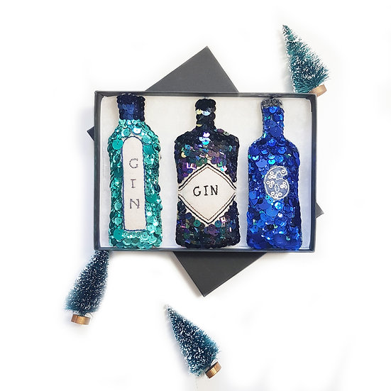 A grey gift box with 3 embroidered hanging ornaments, bombay sapphire, hendrick's and 6 'o' clock gin