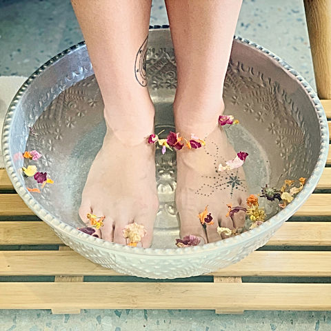 feet soaked in water with flowers