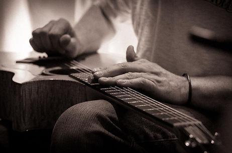 Samuel Tambe playing acoustic guitar