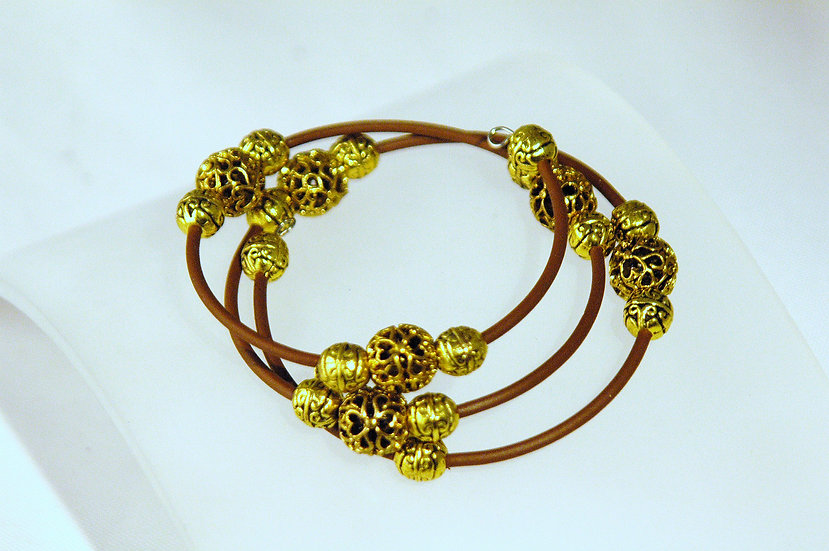 Bracelet wrapped with brown rubber and gold beads