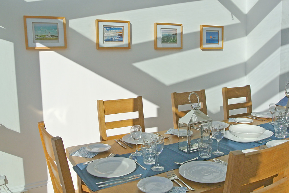Firefly House dining area with prints of IOW