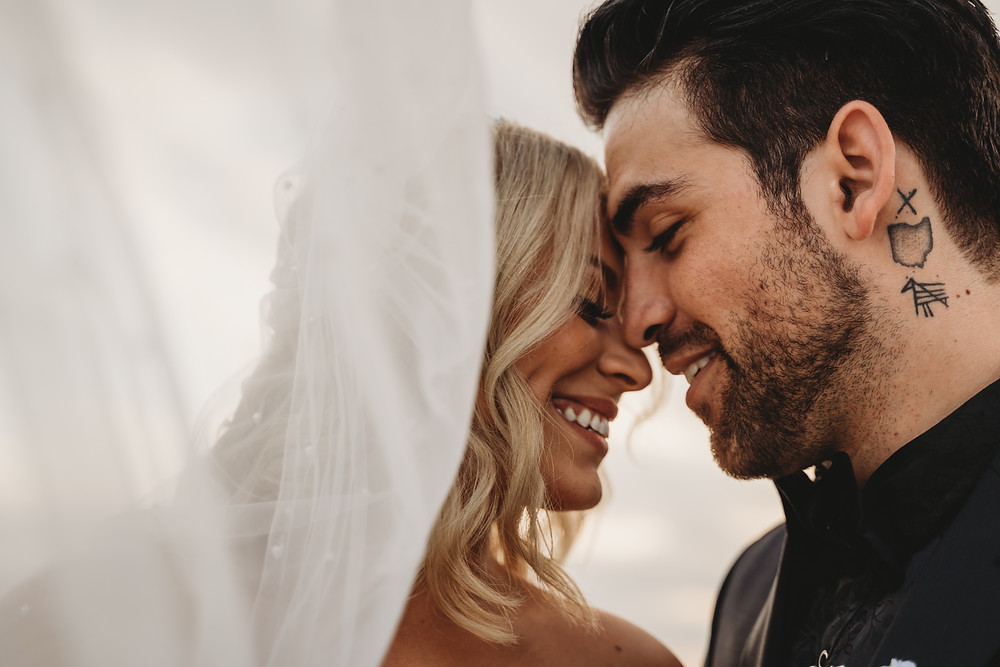 Beautiful tattooed couple snuggle up under veil during beach elopement ceremony in Florida. Blonde hair bride and dark hair groom marry on Halloween.
