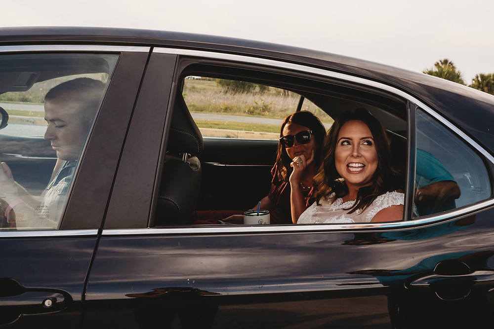 Smiling bride and bridesmaid in shiny black car arrive to Florida beach elopement ceremony.