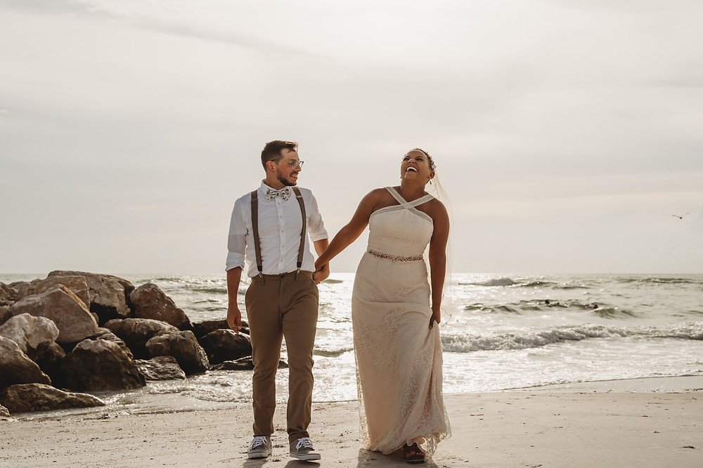 Newly weds on a beach in Florida near a rock jetty holding hands and laughing as they walk.