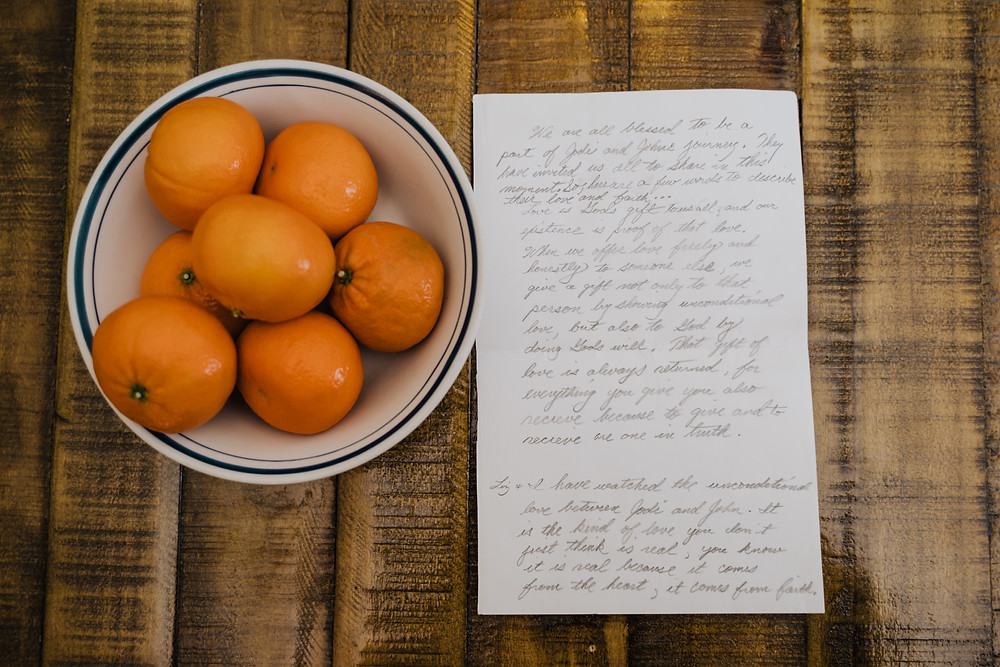 Handwritten note from family to couple getting married next to bowl of Florida oranges during beach elopement celebration.
