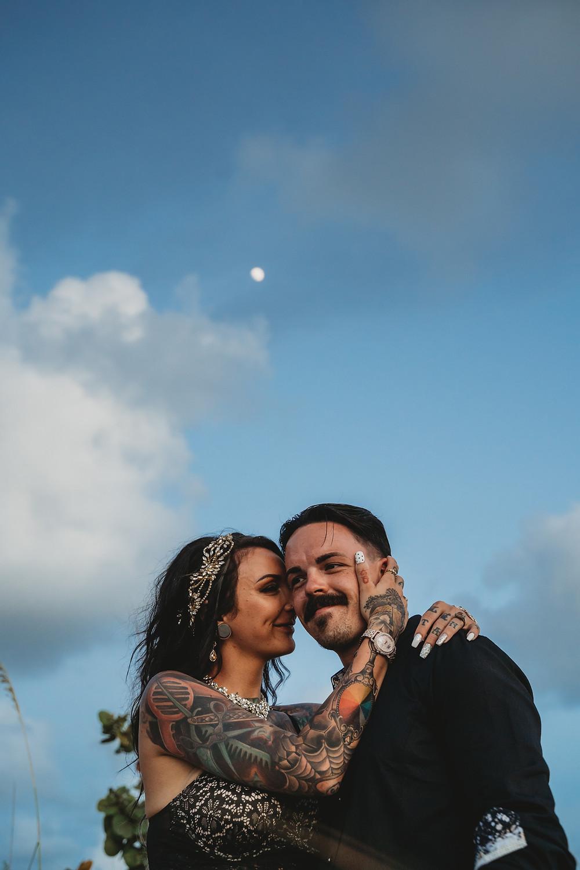 Tattooed bride dressed in black lace hugs groom dressed in black under an almost full moon in Florida.