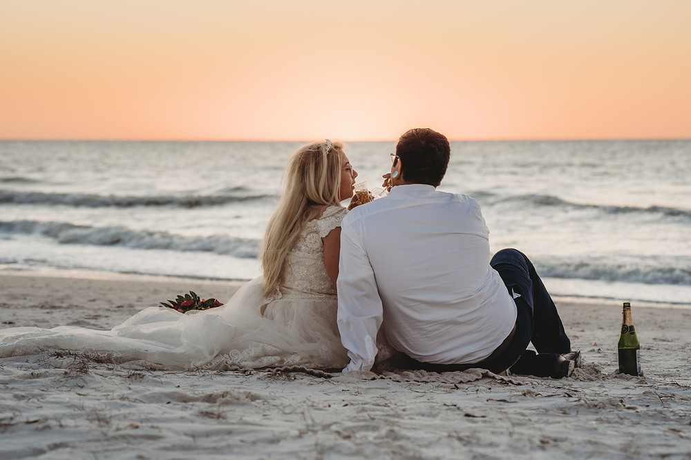 Just married couple sip champagne on Florida beach during sunset elopement marriage ceremony.