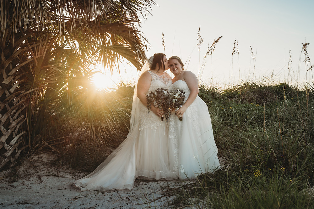 Two brides on a private beach location tucked behind palm trees durning a beautiful Florida Sunset.