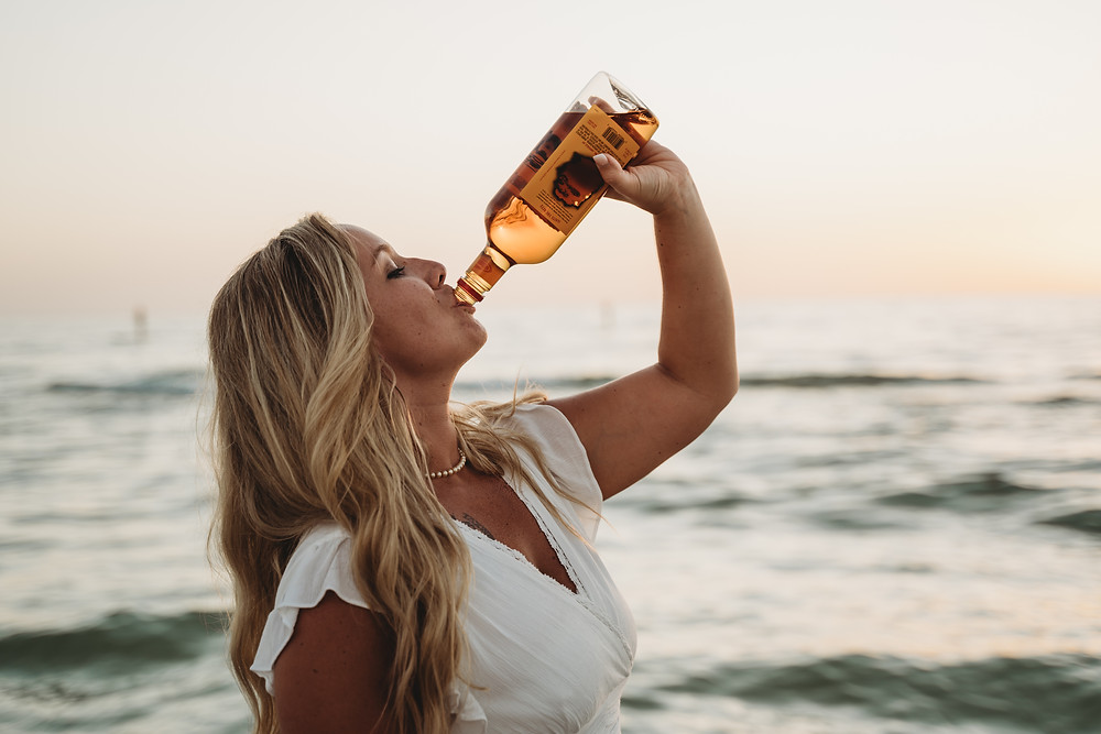 Bride drinking straight from the bottle after a private beach elopement in Florida.