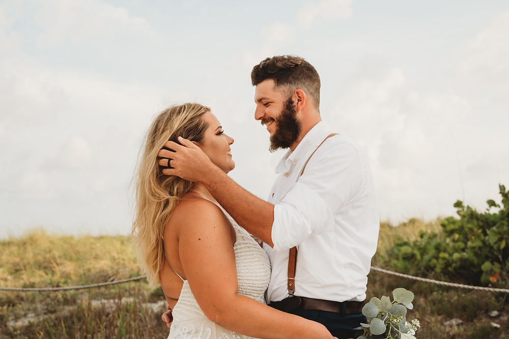 Bearded groom in suspenders with black wedding ring brushes bride's blonde hair off of face during Florida beach elopement.