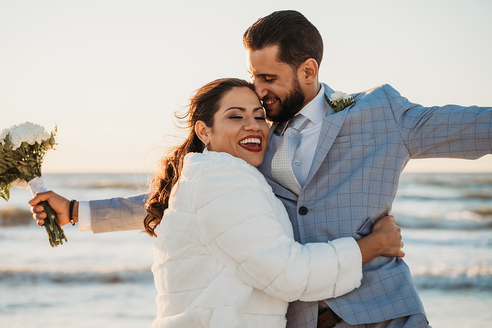 Happy couple on the beach at Florida winter wedding. Bride in faux fur jacket to stay warm hugging groom in blue plaid suit with bouquet.