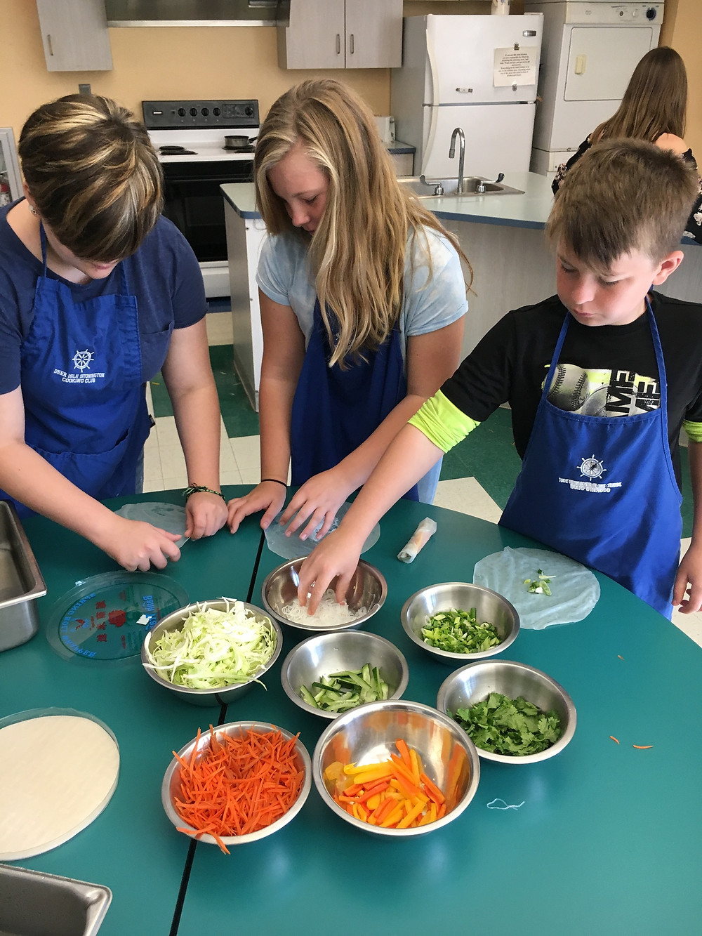 Students construct their own vegetable spring rolls.