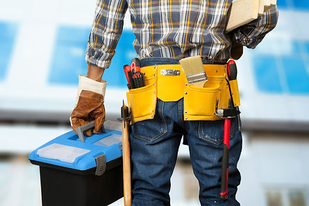 Worker with a tool belt holding a toolbox.