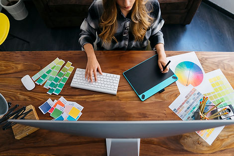 Female graphic designer using a graphics tablet. Color wheel and swatches on desk.