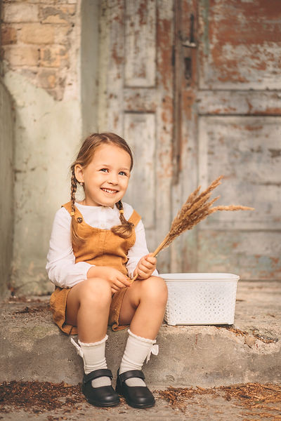 Cute little smiling shy girl sitting on