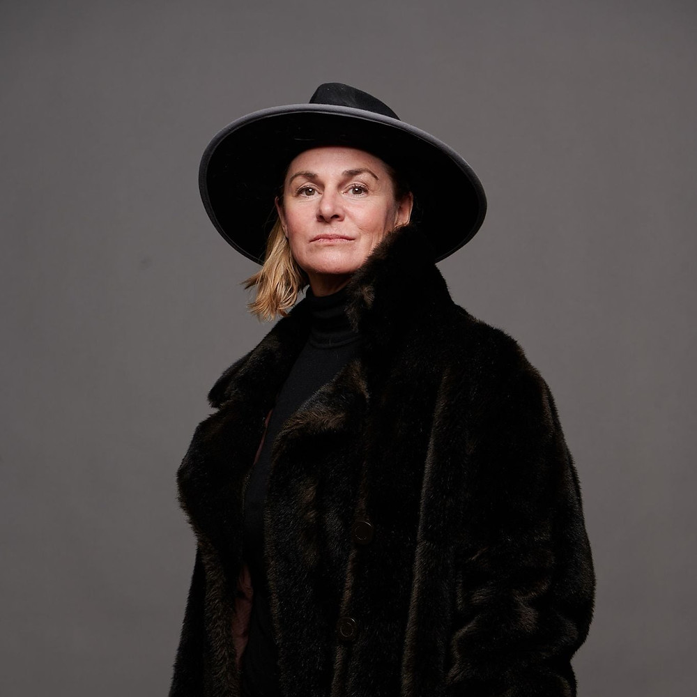 Women with dressed in a big, bulky black fur coat, a wide-brimmed black hat with a white/grey trim, staring straight into the camera, with a knowing look