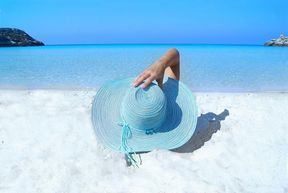Woman on a beach wearing a floppy hat