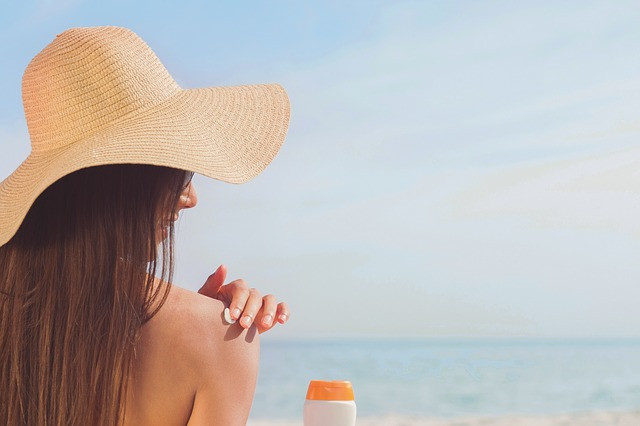 woman applying sunscreen and wearing a floppy hat