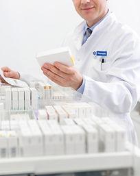 Un pharmacien devant un tirroir de médicaments tient une ordonnance dans la main gauche et une boite de médicments dans la main droite.