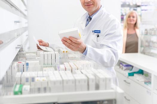 Un farmacista in sta consultando una prescrizione medica mentre cerca un pacchetto di pillole.