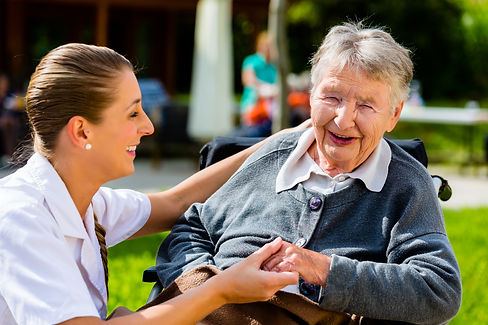 Nurse holding hands with senior woman si