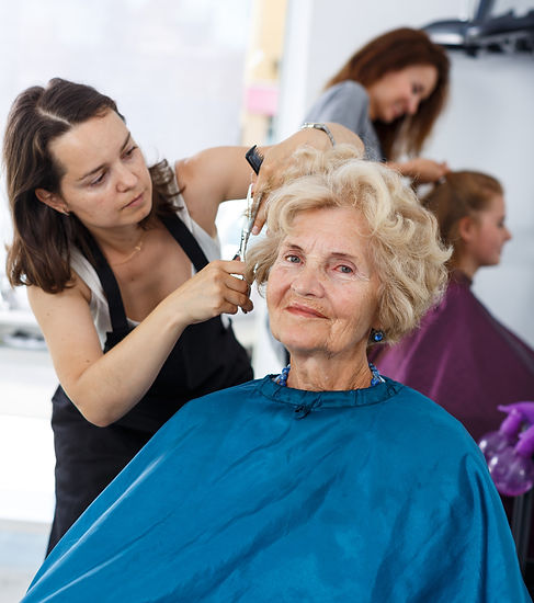 Senior lady getting haircutting by profe