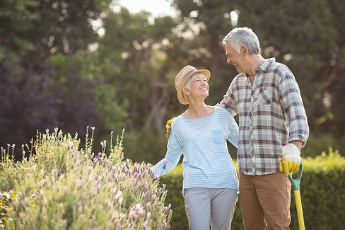 Happy senior couple standing in backyard