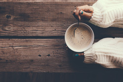Woman holding cup of hot coffee on rustic wooden table, closeup photo of hands in warm sweater with