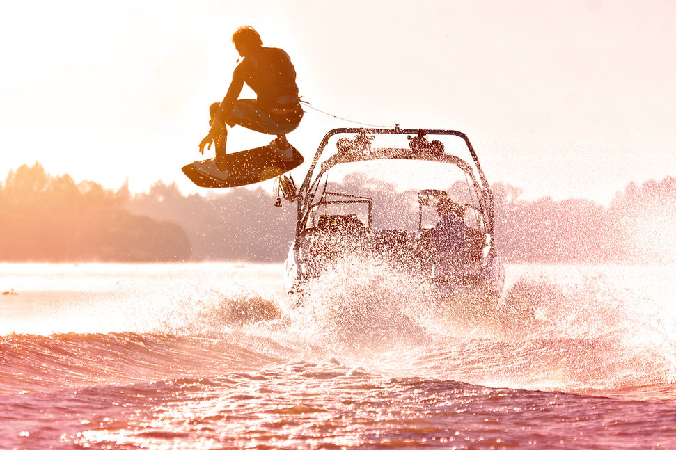 Silhouette of a wake skater as he launches off the wake behind a boat. Added lens flare an