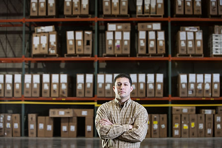 warehouse-worker-by-a-rack-of-stock-in-a-distribut-R42C5ZW.jpg