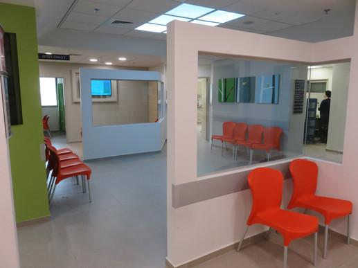 """פינות המתנה במרפאה בבית שמש (כ-500 מ""""ר). הקירות הנמוכים והשקופים מגדירים את איזוורי ההמתנה במסגרת החלל הגדול"""
