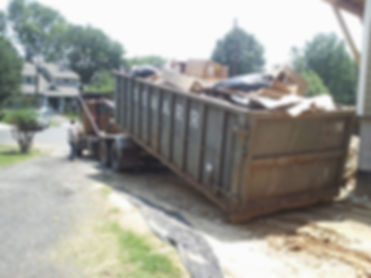 A full 30 cubic yard dumpster being loaded on our rolloff truck.