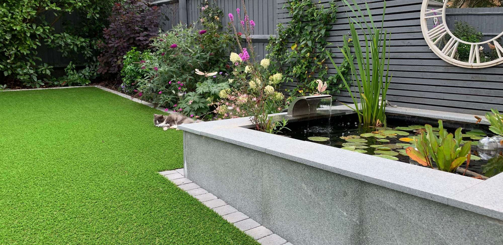 Raised contemporary pond in Bingham with granite faced retaining wall and copings