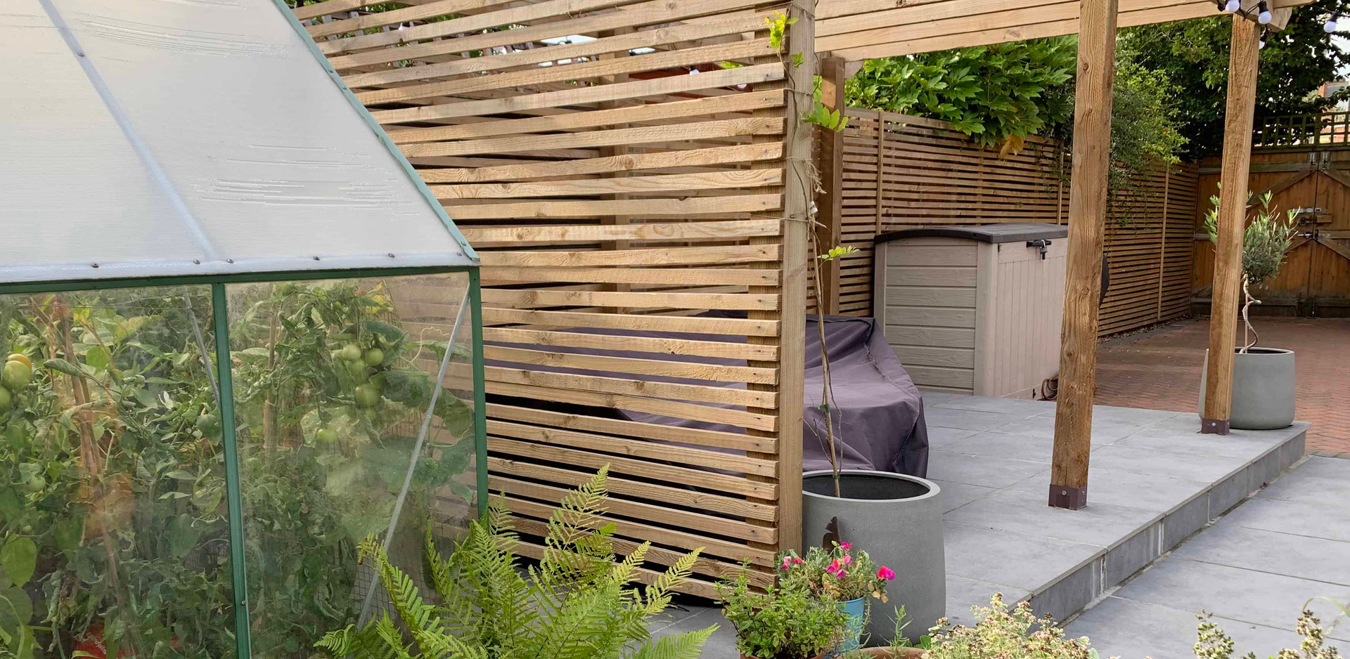 Pergola over porcelain paving with horizontal lath fencing in Carlton