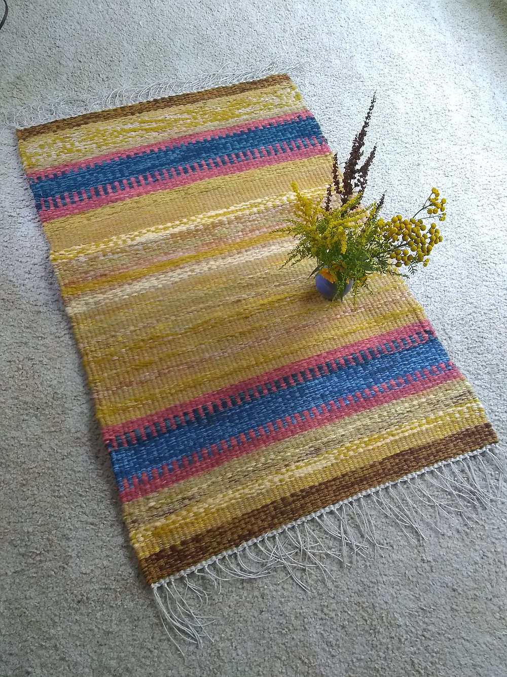 Gold, red, blue and brown striped handwoven rug with fringe.