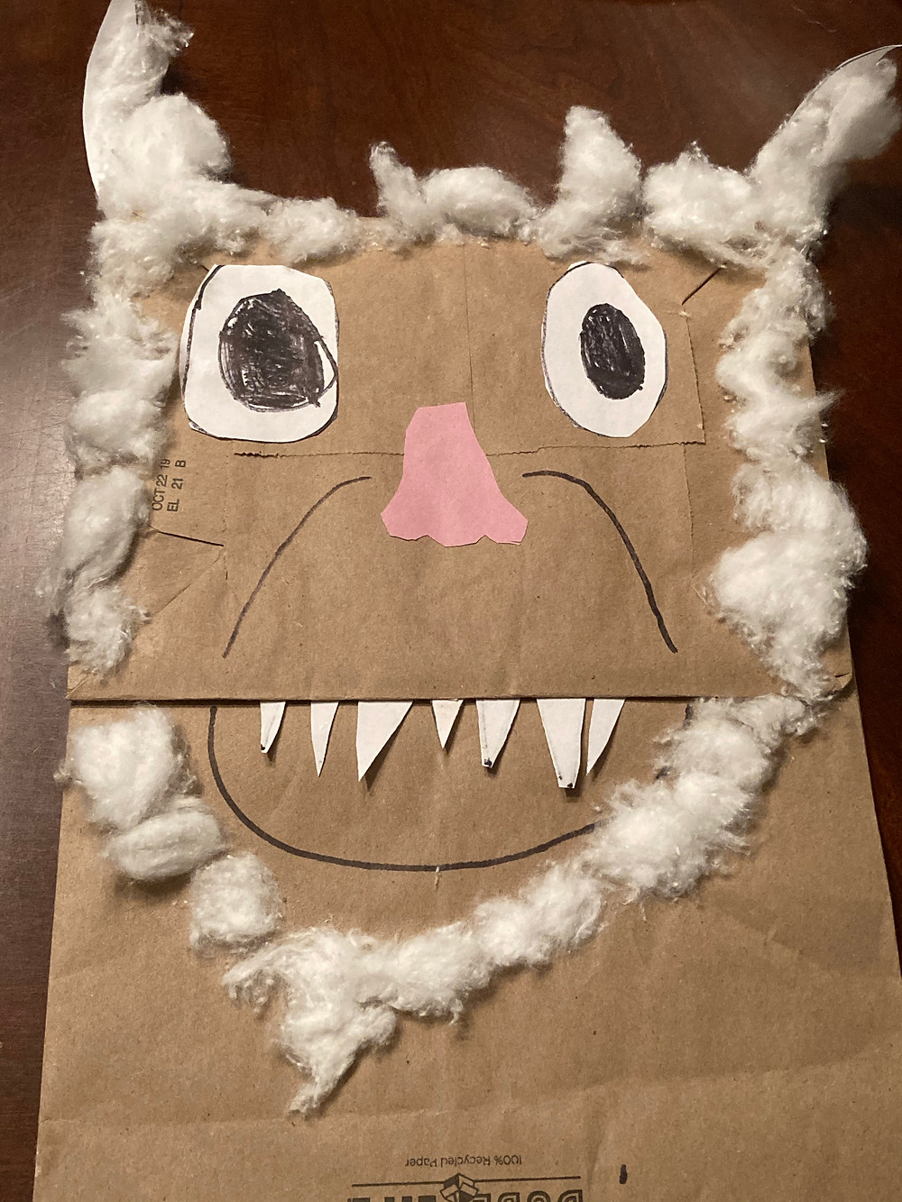 Mixed media representation of wild creature on paper bag.